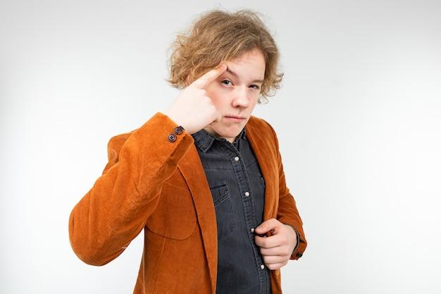 Empörter lockiger blonder kerl in einer braunen jacke erklärt auf einem weißen studiohintergrund