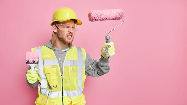 Empörter männlicher baumeister hält reparaturwerkzeuge, die sich über zu viel arbeit ärgern