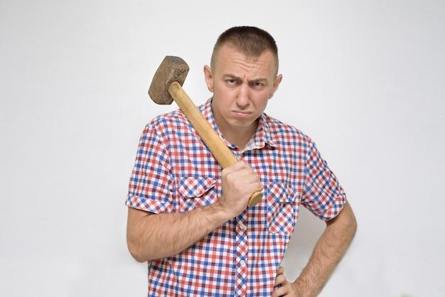 Empörter mann mit einem vorschlaghammer auf einem weiß. arbeit