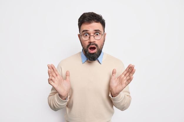 Empörter verwirrter bärtiger erwachsener mann hebt die handflächen, sieht verwirrt aus, hat einen überraschten gesichtsausdruck, kann nicht an etwas unerwartetes glauben, trägt einen lässigen pullover