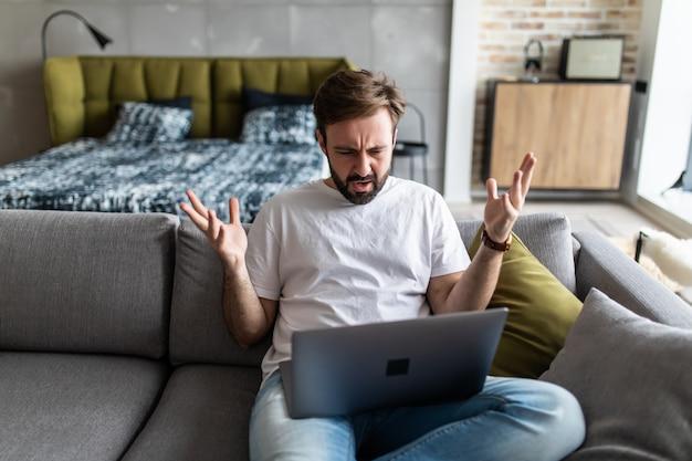 Empörter wütender mann, der schlechte nachrichten liest, auf den bildschirm schaut und ein problem mit einem kaputten laptop hat.