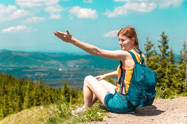 Empörtes müdes mädchen mit einem rucksack sitzt auf einem berg und genießt die schönen hügel des berges an einem sonnigen tag.
