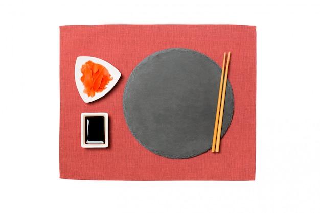 Emptyround-schwarzschieferplatte mit essstäbchen für sushi, ingwer und sojasoße auf roter serviette.