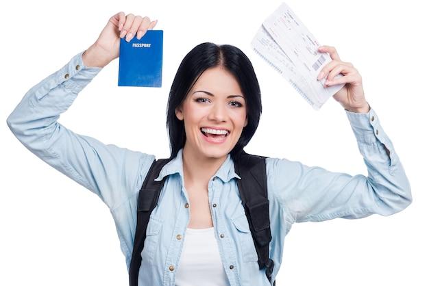 Endlich fahre ich in den urlaub! schöne junge lächelnde frau mit tickets und reisepass im stehen vor weißem hintergrund