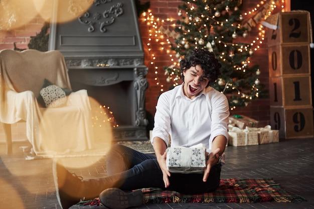 Endlich ferien. der typ ist zufrieden. junger mann, der auf dem boden des schönen verzierten raumes sitzt und weiße geschenkbox in der zeit des neuen jahres hält