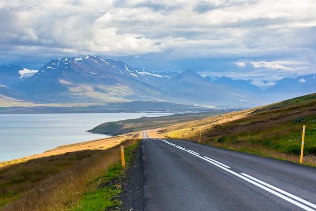 Endlose isländische autobahn mit meerblicklandschaft