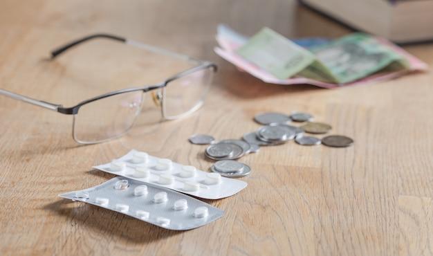 Endpillen und münzen auf kariertem stoff, teure medikamente, geldmangel für medikamente, armut, elend. niedriger lebensstandard, krankheit.