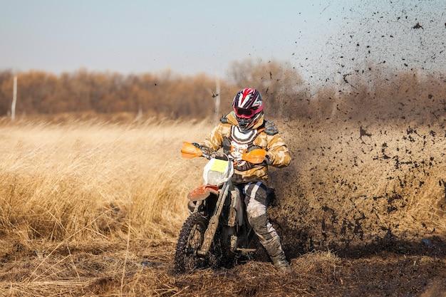 Enduro-fahrer auf einem feld mit trockenem gras im herbst. das motorrad rutscht und macht viele schlammspritzer