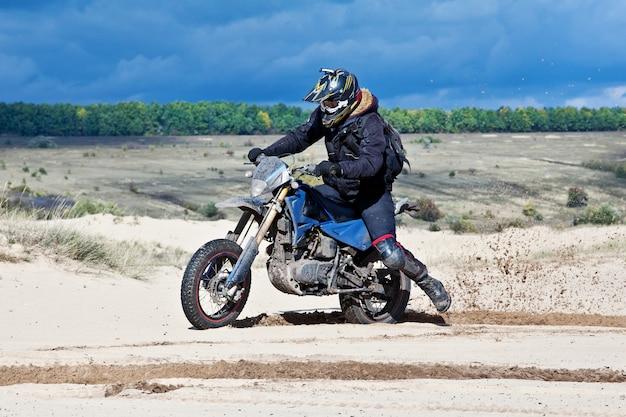 Enduro-fahrer fährt durch die wüste