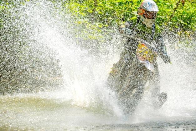 Enduro im sommer. sonniges wetter. der athlet überwindet den bach mit einer großen anzahl von spritzern