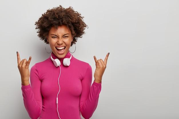 Energetische lockige weibliche meloman macht rock'n'roll-geste, hat freudigen rebellischen ausdruck