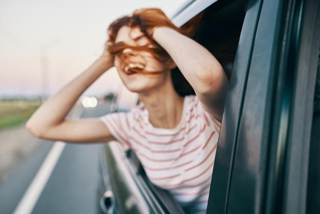 Energetische rothaarige t-shirt-frau, die aus dem offenen autofenster auf der straßenbahnfahrt späht