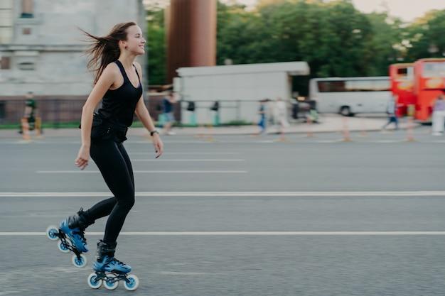 Energetische schlanke junge lächelnde frau rollerblades auf der stadtstraße genießt es, freizeit aktiv zu verbringen, bewegt sich schnell und hat dunkles haar, das auf wind schwimmt, führt zu einem gesunden lebensstil. aktive wochenenden. outdoor-foto