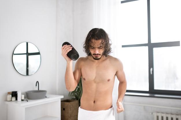 Energetischer kerl mit weißem handtuch auf den hüften und tragbarem drahtlosem bluetooth-lautsprecher, der im badezimmer tanzt