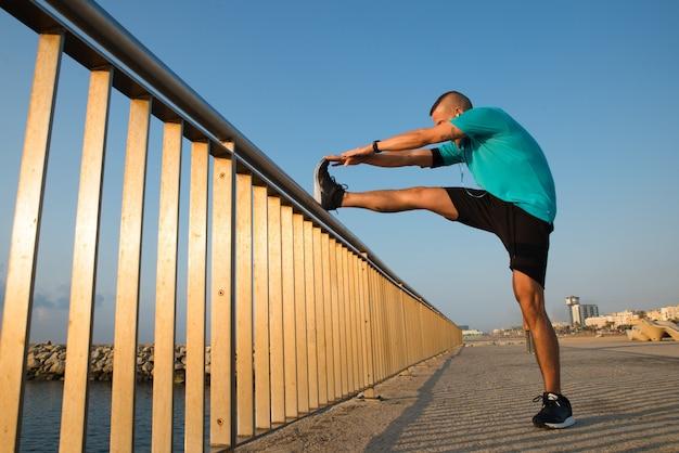 Energetischer männlicher athlet, der sich auf der brücke ausdehnt