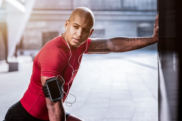 Energetischer rhythmus. hübscher afroamerikanischer mann, der seine lieblingsmusik hört, während er sportübungen macht
