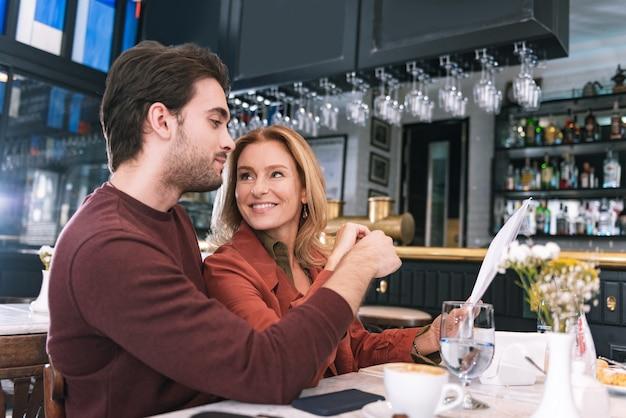 Energetisches entzückendes paar, das mahlzeit auswählt und am tisch aufwirft