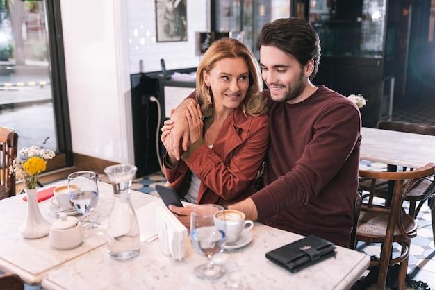 Energetisches fröhliches paar, das im restaurant sitzt und telefon benutzt