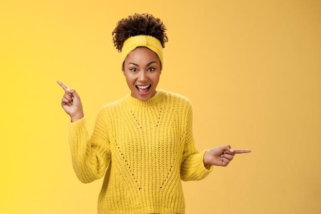 Energetisierte aktive charismatische afroamerikanische frau afro-frisur in pullover stirnband schreien fasziniert enthusiastisch nach links rechts zeigend beeindruckt verschiedene tolle entscheidungen, produkte auswählen.