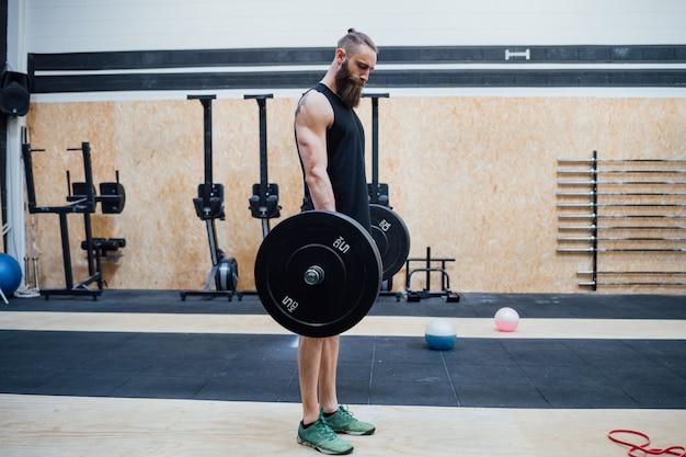 Energie des jungen mannes, die innengymnastik allein ausbildend anhebt - body building, eignung, kreuz-sitzkonzept