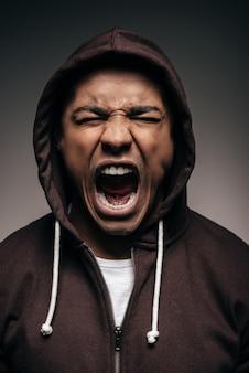Energie in ihm. wütender junger afrikaner in kapuzenhemd, der die augen geschlossen hält und schreit