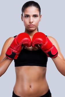 Energie in ihr. attraktive junge sportliche frau in boxhandschuhen, die eine kunstkamera sucht, während sie vor grauem hintergrund steht