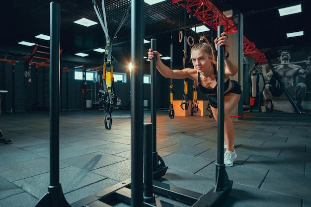 Energie. junge muskulöse kaukasische frau, die im fitnessstudio mit den gewichten übt. sportliches weibliches model, das kraftübungen macht und ihren unter- und oberkörper trainiert. wellness, gesunder lebensstil, bodybuilding.