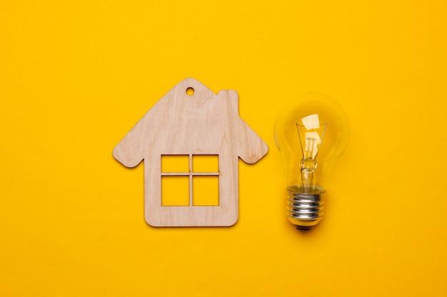 Energie sparen konzept. mini-haus, glühbirne auf gelbem hintergrund. draufsicht
