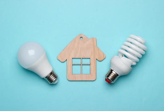 Energie sparen konzept. öko-haus-konzept. mini-haus und energiesparlampe auf blauem hintergrund