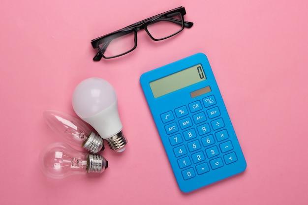 Energie sparen. rechner mit glühbirnen, brille auf rosa blau pastell