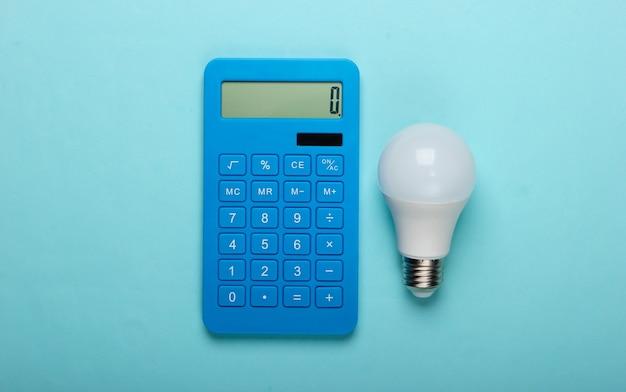 Energie sparen. rechner mit led-glühbirne auf einem blauen pastellhintergrund. draufsicht