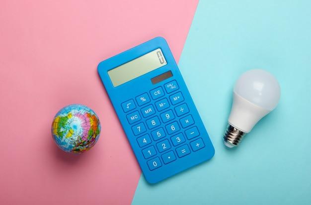 Energie sparen. rechner mit led-glühbirne und globus auf blau-rosa pastellhintergrund. rette den planeten. öko-konzept. draufsicht