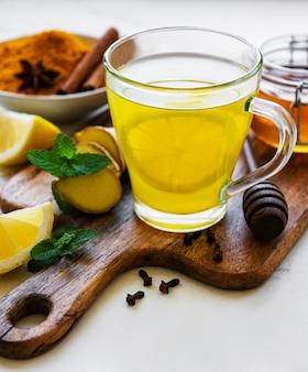 Energie-tonic-getränk mit kurkuma, ingwer, zitrone und honig auf einem weißen marmorhintergrund