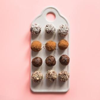 Energiebälle mit kakao und nüssen auf rosa.