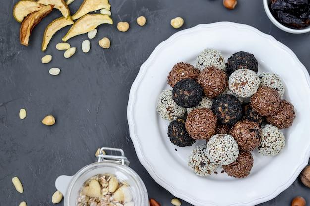Energiebälle von nüssen, von hafermehl und von trockenfrüchten auf einer platte