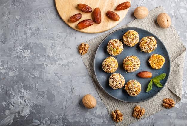 Energieballkuchen mit getrockneten aprikosen, indischem sesam, leinen, walnüssen und daten auf grauem beton