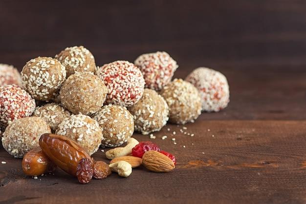 Energiebissen von datteln, cashewnüssen, rosinen, preiselbeeren und mandeln auf dunklem holztisch