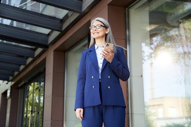 Energiegeladene frau mittleren alters, die begeistert aussieht und bereit ist, einen neuen arbeitstag im büro zu beginnen