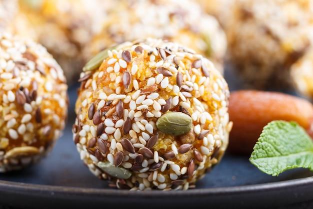 Energiekuchen mit getrockneten aprikosen, indischem sesam, walnüssen und daten auf einer keramischen platte