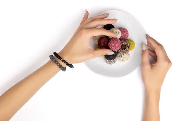 Energiekugeln der bunten veganen bonbons auf platte mit lokalisiertem weiß der hand der frau