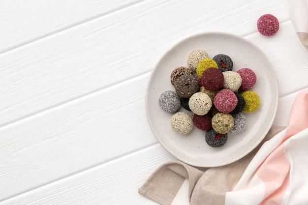 Energiekugeln der bunten veganen bonbons auf teller auf weißem holztisch