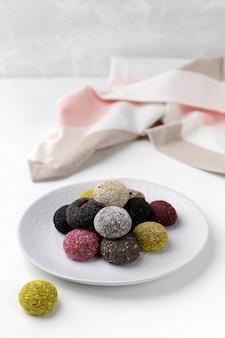 Energiekugeln der bunten veganen bonbons auf teller auf weißem tisch