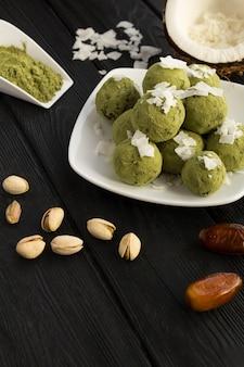 Energiekugeln mit matchapulver, pistazien, datteln und kokosnusschips in der weißen platte auf dem schwarzen holztisch.