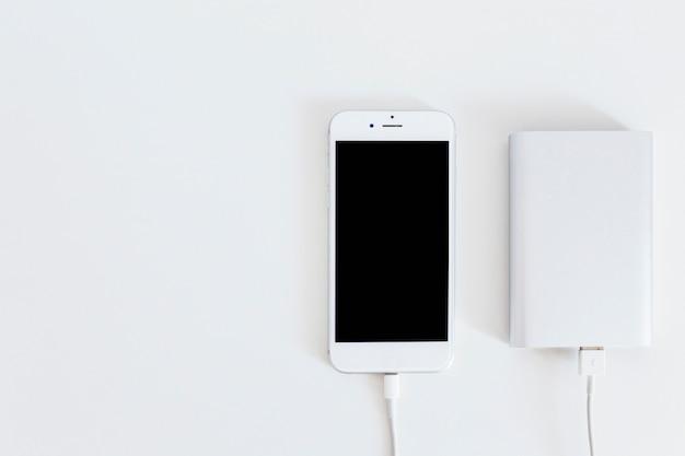 Energienbank, die intelligentes telefon über dem weißen hintergrund auflädt