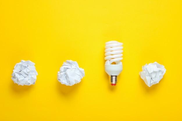 Energiesparende glühbirne und zerknitterte papierkugeln auf gelbem tisch. minimalistisches geschäftskonzept, idee. draufsicht