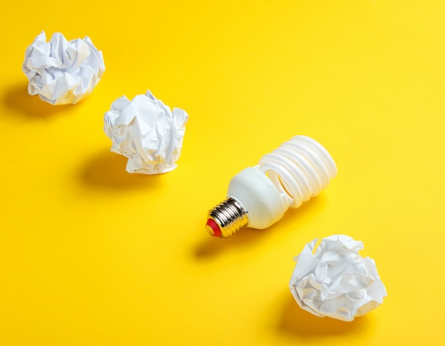 Energiesparende glühbirne und zerknitterte papierkugeln auf gelbem tisch. minimalistisches geschäftskonzept, idee