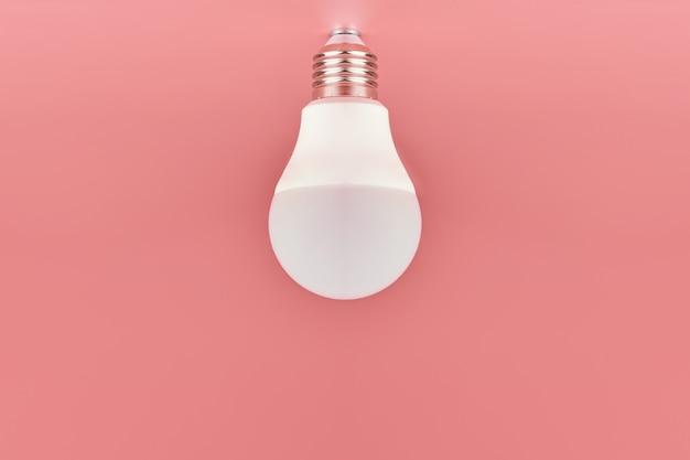 Energiesparende glühlampe auf rosa hintergrund