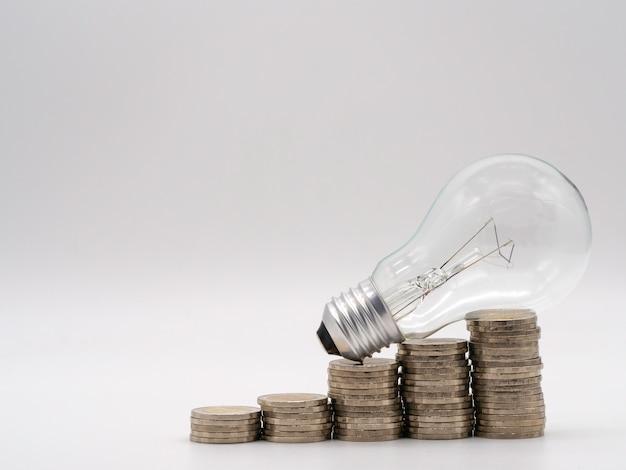 Energiesparende glühlampe mit stapeln münzen für finanz-, buchhaltungs- und einsparungskonzept.