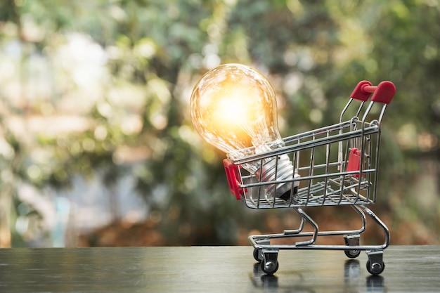 Energiesparende glühlampe mit warenkorb finanz- und einkaufskonzept