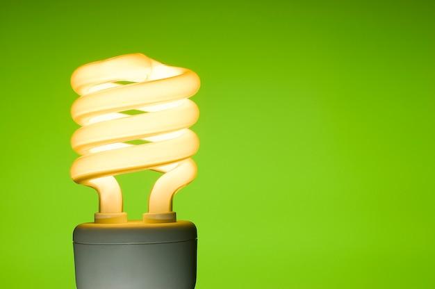 Energiesparende leuchtstofflampe auf grünem hintergrund.